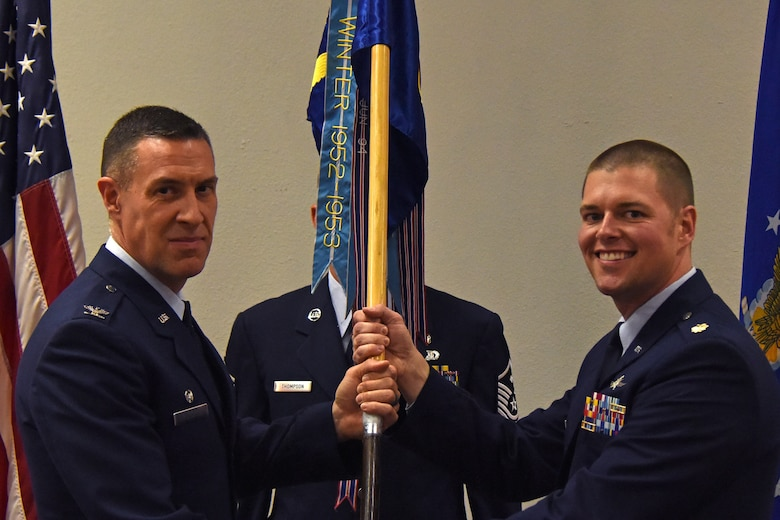 U.S. Air Force Col. Jason Beck, 17th Mission Support Group commander, presents the guideon to Maj. David Coté, 17th Communications Squadron commander, during the change of command ceremony in the Event center on Goodfellow Air Force Base, Texas, May 10, 2018. The change of command ceremony is a time honored military tradition that signifies the orderly transfer of authority. (U.S. Air Force photo by Airman 1st Class Zachary Chapman/Released)