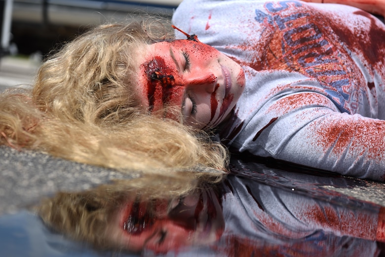 A student performer plays dead as a result of a drunk driving car crash during Freshman Impact at Douglas High School, Box Elder S.D., May 9, 2018. This event teaches young adults the dangers of driving under the influence and distracted driving so they can make better decisions behind the wheel. (U.S.  Air Force photo by Airman 1st Class Thomas Karol)