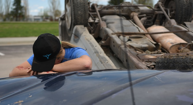 A student performer pretends to cry after causing a simulated vehicle accident at Douglas High School's Freshman Impact in Box Elder S.D., May 9, 2018. An event called Freshmen Impact teaches young adults about the dangers of driving under the influence and distracted driving so they can make better decisions while behind the wheel. (U.S.  Air Force photo by Airman 1st Class Thomas Karol)