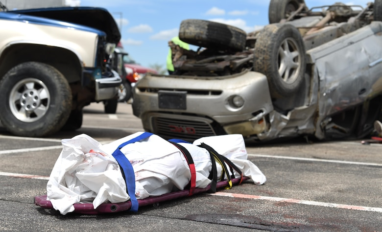 A student performer lays in a body bag during Freshman Impact at Douglas High School, Box Elder S.D., May 9, 2018. This event teaches young adults about the dangers of driving under the influence and distracted driving so they can make better decisions while behind the wheel. (U.S.  Air Force photo by Airman 1st Class Thomas Karol)