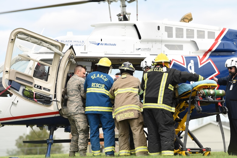 A student performer is loaded in to a medical helicopter during Douglas High School's Freshman Impact in Box Elder S.D., May 9, 2018. This event teaches young adults about the dangers of driving under the influence and distracted driving so they can make better decisions behind the wheel. (U.S.  Air Force photo by Airman 1st Class Thomas Karol)
