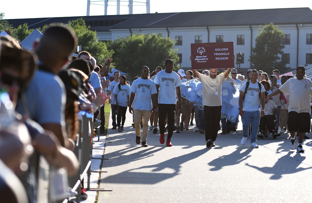 Athletes and Airmen sponsors make their way down the troop walk during the Special Olympics Mississippi 2018 Summer Games opening ceremony at the Training Levitow Training Support Facility drill pad at Keesler Air Force Base, Mississippi, May 11, 2018. Founded in 1968, Special Olympics hosts sporting events around the world for people of all ages with special needs to include more than 700 athletes from Mississippi. (U.S. Air Force photo by Kemberly Groue)