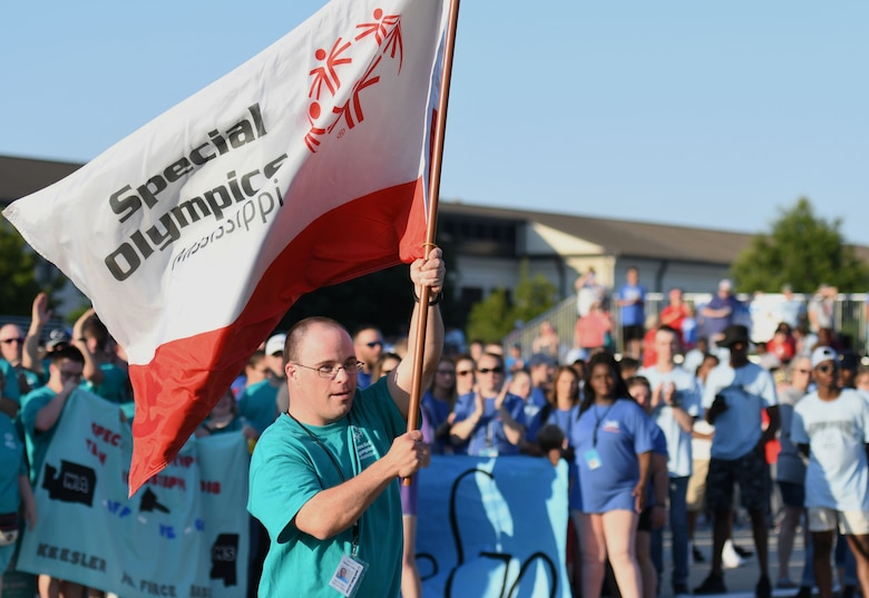Danny Dasis, Area 5 athlete, carries the Special Olympics flag during the Special Olympics Mississippi 2018 Summer Games opening ceremony at the Training Levitow Training Support Facility drill pad at Keesler Air Force Base, Mississippi, May 11, 2018. Founded in 1968, Special Olympics hosts sporting events around the world for people of all ages with special needs to include more than 700 athletes from Mississippi. (U.S. Air Force photo by Kemberly Groue)