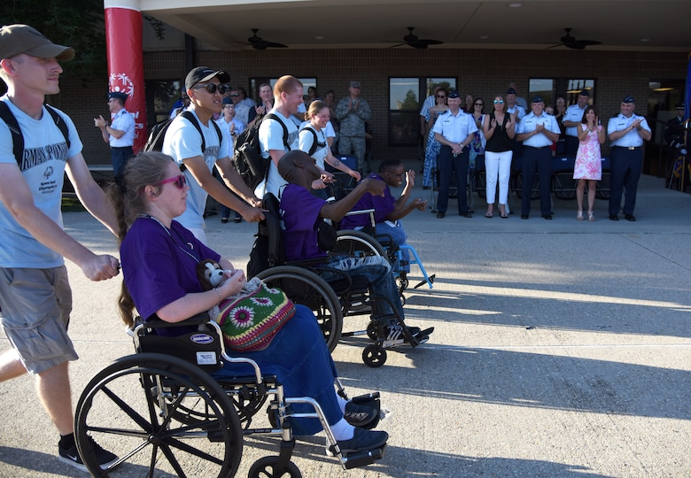 Keesler leadership cheer on athletes and their Airmen sponsors as they make their way down the troop walk during the Special Olympics Mississippi 2018 Summer Games opening ceremony at the Training Levitow Training Support Facility drill pad at Keesler Air Force Base, Mississippi, May 11, 2018. Founded in 1968, Special Olympics hosts sporting events around the world for people of all ages with special needs to include more than 700 athletes from Mississippi. (U.S. Air Force photo by Kemberly Groue)