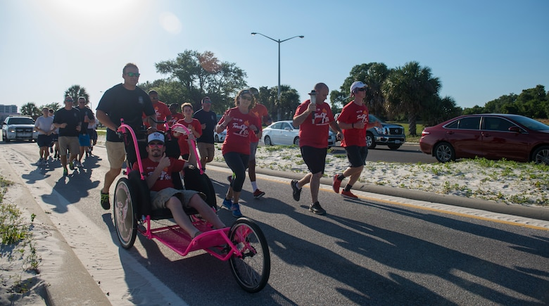 Mississippi police officers and Special Olympics Mississippi athletes run during the SOMS 2018 Summer Games torch run in Biloxi, Mississippi, May 11, 2018. Founded in 1968, Special Olympics hosts sporting events around the world for people of all ages with special needs to include more than 700 athletes from Mississippi. (U.S. Air Force photo by Senior Airman Travis Beihl)