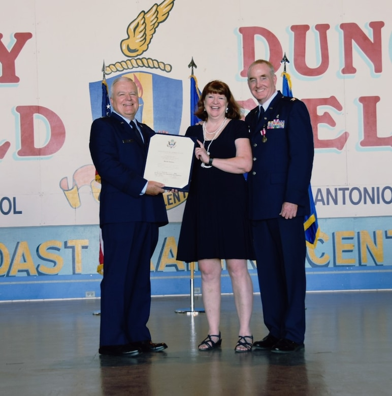 Brig. Gen. John C. Fobian, former 433rd commander, presented Mrs. Sarah Nelson, a spouse certificate of appreciation alongside her husband Col. Michael Nelson, 433rd Medical Squadron commander, May 5, 2018 at Joint Base San Antonio, Texas. Nelson began his Air Force career at Kelly Air Force Base, Texas as an enlisted Airman as a bioenvironmental engineering specialist. (U.S. Air Force photo by Tech. Sgt. Carlos J. Trevino)
