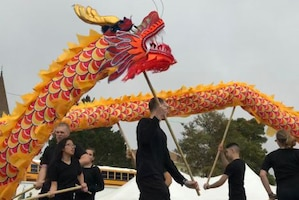 People wearing all black carry maneuver a red and orange dragon puppet held on sticks.