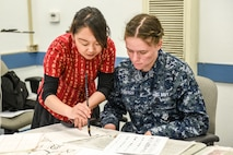 Cong Li, Defense Language Institute assistant Chinese professor, demonstrates how to write Chinese characters to Seaman Madelyn Nizenberger, Navy detachment trainee, during Defense Language Institute Foreign Language Center Language Day at the Presideo of Monterey, California, May 11, 2018. In addition to dances, music, and cultural tents, Language Day also included classroom demonstrations.
