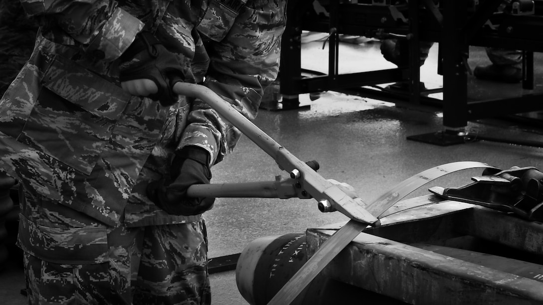 An Airman participating in Combat Ammunition Production Exercise 2018 cuts a wire on a container of munition bodies that have been disassembled on Gwangju Air Force Base, Gwangju, Republic of Korea, May 7, 2018.