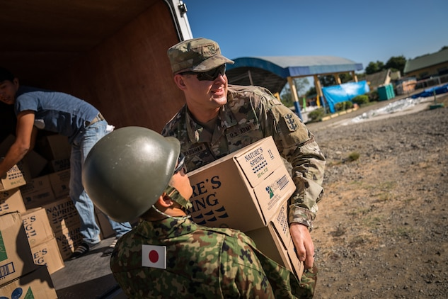 United States and Japan Ground-Self Defense Force soldiers unload boxes of water from a supply truck at Cabu Elementary School in Cabanatuan City, Nueva Ecija, Philippines, in support of Exercise Balikatan, April 20, 2018.