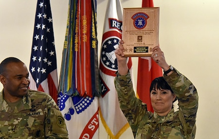 Two soldiers standing next to each other one is holding a plaque in the air above her head