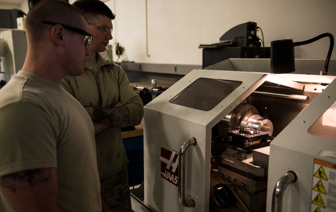 Staff Sgt. Steven Doucette, 92nd Maintenance Squadron aircraft metals technology shift lead, and Staff Sgt. Steven Bultemeier, 92nd MXS aircraft metals technology craftsman, use the Computer Numerically Controlled lathe April 26, 2018, at Fairchild Air Force Base, Washington. The CNC lathe is imperative to reverse engineering and manufacturing the main inlet fuel coupling needed to refuel coalition aircraft. (U.S. Air Force photo/Senior Airman Sean Campbell)