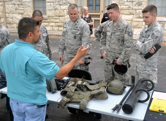 U.S. Marshal Marc Seguin (left) talks about some of the equipment he uses to Security Forces members at the opening of National Police Week May 15 at the Quadrangle at Joint Base San Antonio-Fort Sam Houston.