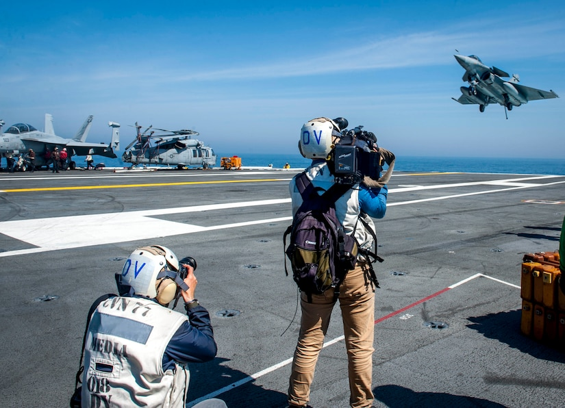 French media gather imagery and footage as a Rafale French navy aircraft attached to prepares to launch during flight operations aboard the aircraft carrier USS George H.W. Bush in the Atlantic Ocean.