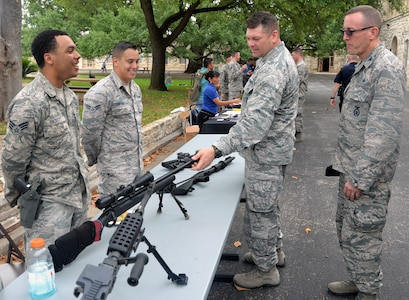 Col. Brian Barthel (right), Chief, Security Force, Air Education and Training Command, and Col. Thomas Miner (second from right), commander, 502nd Security and Readiness Group, look over some of the weapons used by 502nd Security Forces Squadron members at the opening of National Police Week at the Quadrangle at Joint Base San Antonio-Fort Sam Houston May 14.