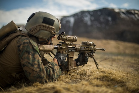 A U.S. Marine with 1st Platoon, 1st Reconnaissance Battalion, 1st Marine Division, returns fire while conducting a live fire range and patrol, during Exercise Platinum Ren, at Fort Trondennes, Harstad, Norway, May 11, 2018.