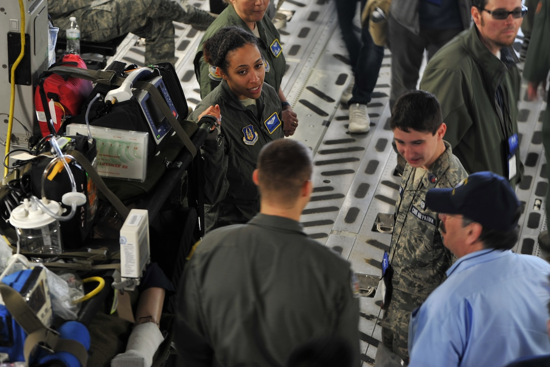 Senior Airman Jazmyn Anderson, flight medic with the 439th Aeromedical Evacuation Squadron, shares information with teenage students and chaperones visiting the C-17 Globemaster III static display during the Alaska Airlines Aviation Day event May 5, 2018 at Seattle-Tacoma International Airport.