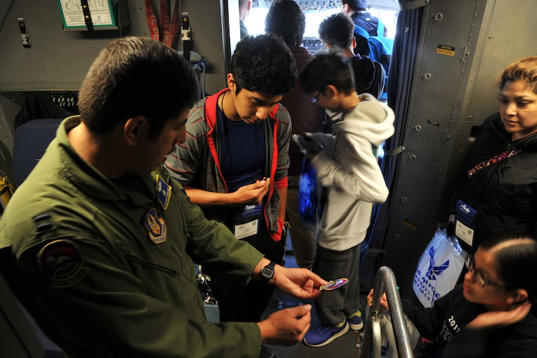 Capt. Lazare Quintana, C-17 Globemaster III pilot with the 313th Airlift Squadron, explains the elements of the squadron patch before handing it out to teenage students visiting the C-17 static display during the Alaska Airlines Aviation Day event May 5, 2018 at Seattle-Tacoma International Airport.
