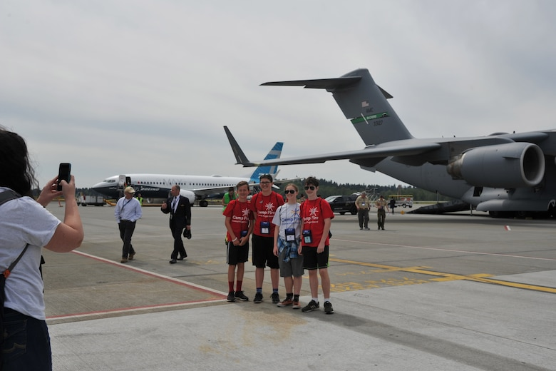 Stacy Cotton, chaperone, takes a photo of members of Robot Camperz, a co-ed group of Camp Fire Central Puget Sound, in front of the C-17 Globemaster III static display during the Alaska Airlines Aviation Day event May 5, 2018 at Seattle-Tacoma International Airport.