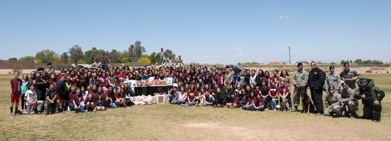 Members of L. Thomas Heck Middle School's sixth-grade class pose for a photo with members of the 56th Security Forces Squadron and 56th Civil Engineer Squadron explosive ordnance disposal flight April 20, 2018, in Litchfield Park, Ariz. The table in the center contained food and entertainment items to be sent in care packages to deployed service members. (U.S. Air Force photo by Senior Airman Ridge Shan)