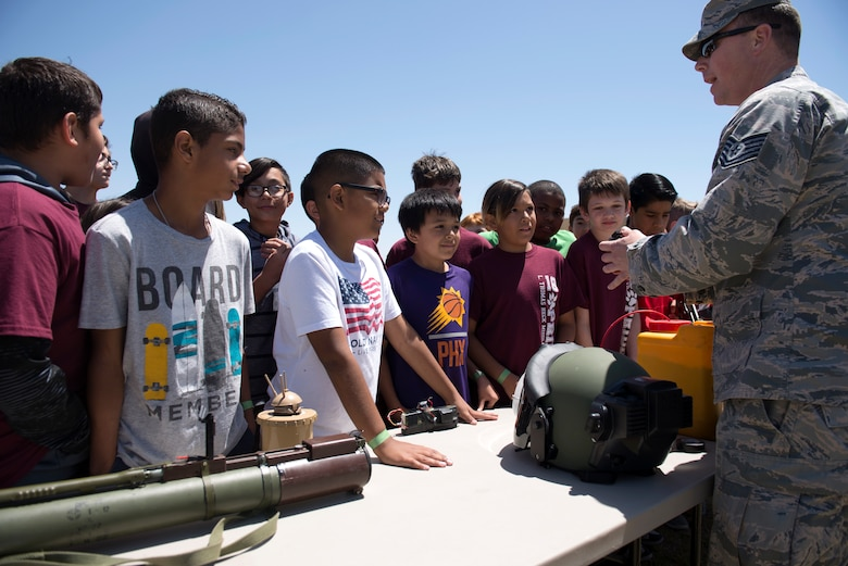 A 56th Civil Engineer Squadron explosive ordnance disposal technician talks about his equipment and work with a group of students from L. Thomas Heck Middle School April 20, 2018, in Litchfield Park, Ariz. The 56th CES EOD joined several flights of Airmen from the 56th Security Forces Squadron in visiting the middle school. (U.S. Air Force photo by Senior Airman Ridge Shan)