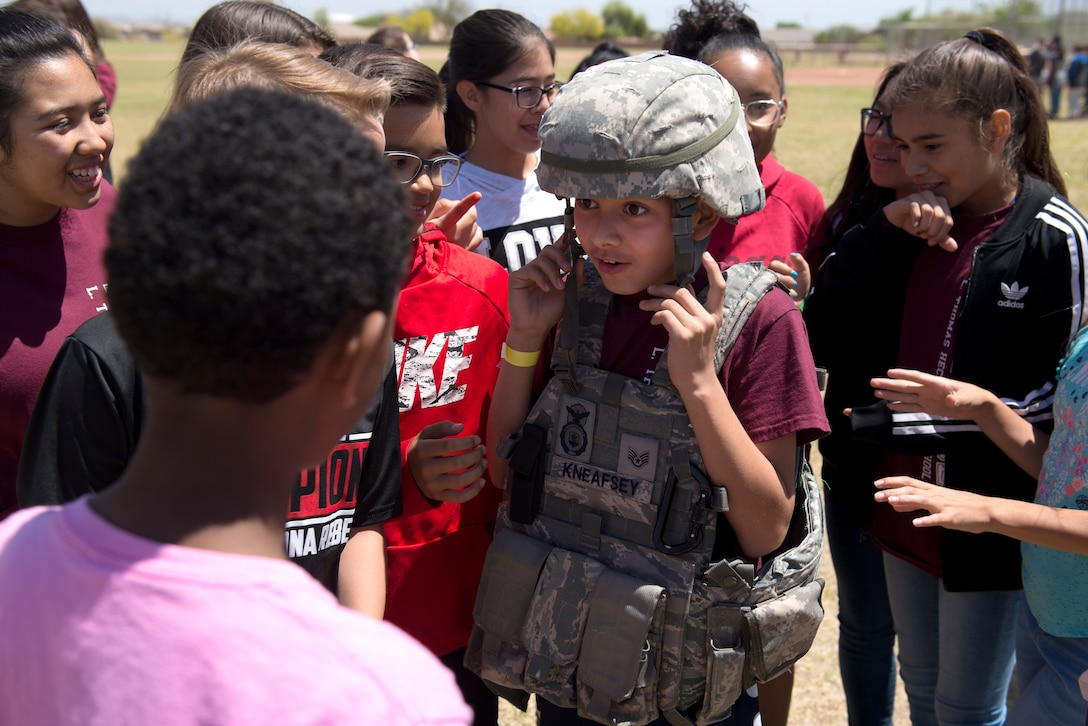 A student tries on the protective vest and helmet of a 56th Security Forces Squadron patrolman April 20, 2018, at L. Thomas Heck Middle School, Litchfield Park, Ariz. The 56th SFS and a group of explosive ordnance disposal Airmen from the 56th Civil Engineer Squadron provided displays for students who collected food and entertainment material to send care packages to deployed service members. (U.S. Air Force photo by Senior Airman Ridge Shan)
