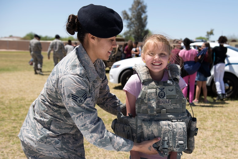 Senior Airman Melissa Ledezma, 56th Security Forces Squadron patrolman, helps a student from L. Thomas Heck Middle School try on her protective vest April 20, 2018, in Litchfield Park, Ariz. The 56th SFS brought vehicles, protective wear, and a military working dog to show off to students during their visit to the school. (U.S. Air Force photo by Senior Airman Ridge Shan)