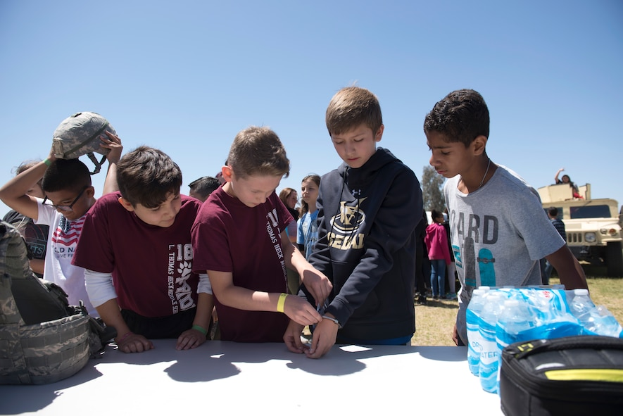 Students from L. Thomas Heck Middle school fiddle with police handcuffs during the 56th Security Forces Squadron visit April 20, 2018, in Litchfield Park, Ariz. Students from each grade had a chance to interact with and learn from Luke Air Force Base Airmen. (U.S. Air Force photo by Senior Airman Ridge Shan)