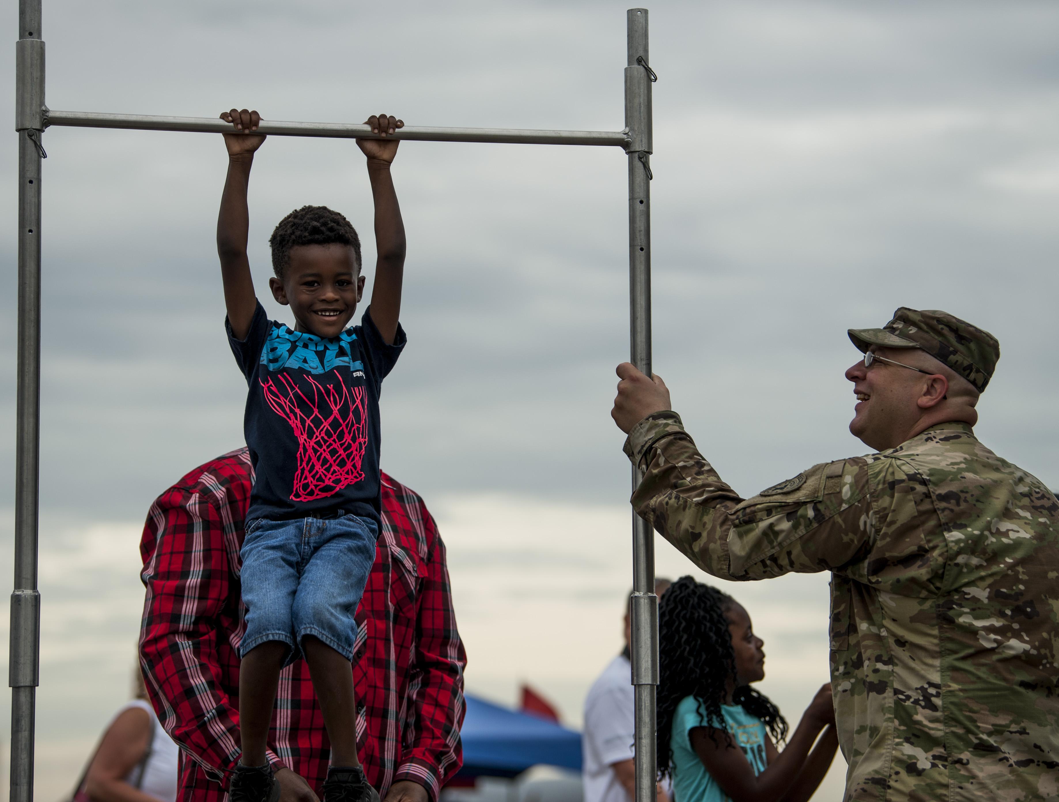 998ad7af369 A child tries out a pull-up bar at a U.S. Army recruitment tent during