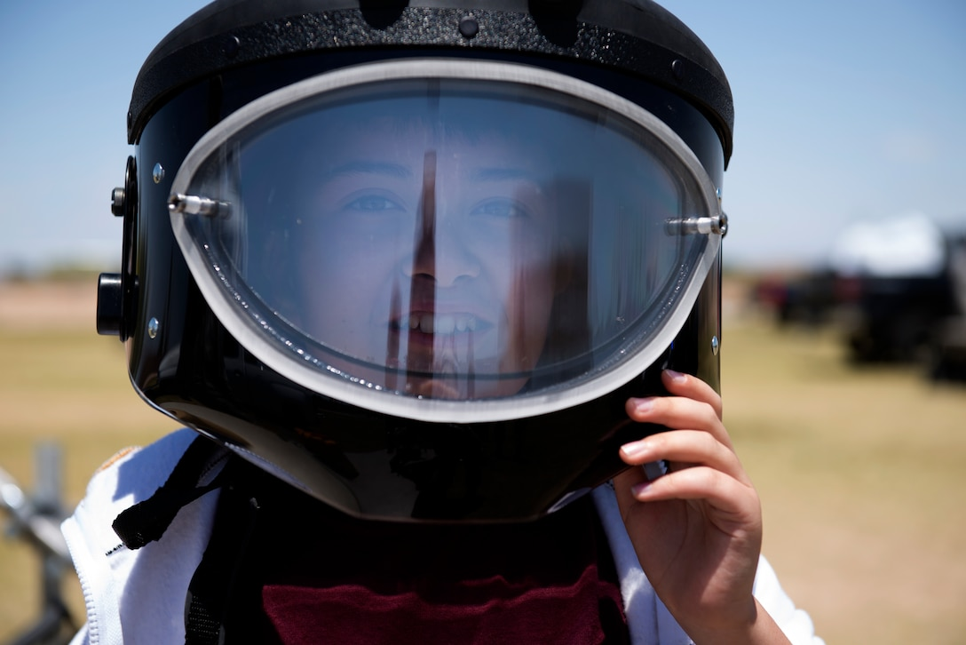 A student from L. Thomas Heck Middle School smiles through the visor of a 56th Civil Engineer Squadron explosive ordnance disposal bomb suit helmet April 20, 2018, in Litchfield Park, Ariz. Students could try on suits, uniform items, and other protective wear commonly used by Luke Air Force Base Airmen. (U.S. Air Force photo by Senior Airman Ridge Shan)