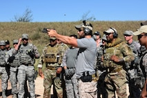 The Shooting Institute chief executive officer, Jared Hudson, demonstrates how to fire a pistol during the Special Weapons and Tactics and Close Quarters Combat training at the Goodfellow Air Force Base shooting range in San Angelo, Texas, May 9, 2018. Students learned how to properly handle a pistol to hit targets quickly, without harming non-targets. (U.S. Air Force photo by Airman 1st Class Seraiah Hines/Released)