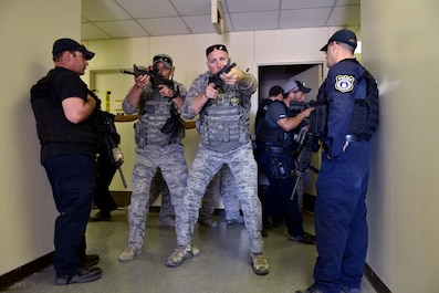 U.S. Air Force Staff Sgt. Mark Riley, 17th Security Forces Squadron unit trainer, and Tech Sgt. Mark Karas, 17th SFS noncommissioned officer in charge, perform close quarters combat maneuvers during the Special Weapons and Tactics and Close Quarters Combat training at the Eldorado Air Force Station in Eldorado, Texas, May 10, 2018. The training would start in a classroom, then move to a firing range or the Eldorado Air Force Station. There, the students would implement their training with drills and simulation rounds. (U.S. Air Force photo by Senior Airman Randall Moose/Released)