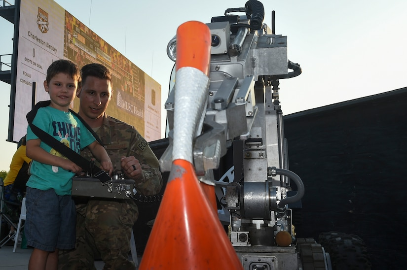 Staff Sgt. Matthew Koser, right, 628th Civil Engineer Squadron Explosive Ordnance Disposal Flight technician, shows four-year-old Jack Plett how to operate one of the EOD robots by clamping onto a traffic cone during the Charleston Battery Military Appreciation Night game at the MUSC Health Stadium on Daniel Island in Charleston, S.C., May 12, 2018. The military appreciation night allowed all military members to attend the soccer game for free. The Charleston Battery won against Bethlehem Steel 2-1.