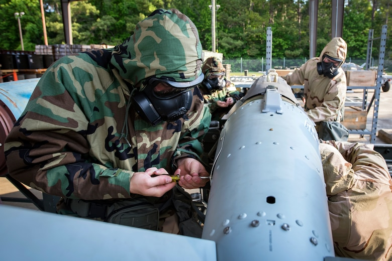 Airmen from the 23d Maintenance Squadron attach components to a Joint-Direct Attack Munition (JDAM) during a bomb building course, May 10, 2018, at Moody Air Force Base, Ga. To ensure readiness to complete their mission efficiently, Airmen practiced constructing a JDAM while wearing Mission Oriented Protective Posture gear to further simulate what their mission could entail.   (U.S. Air Force photo by Airman 1st Class Eugene Oliver)