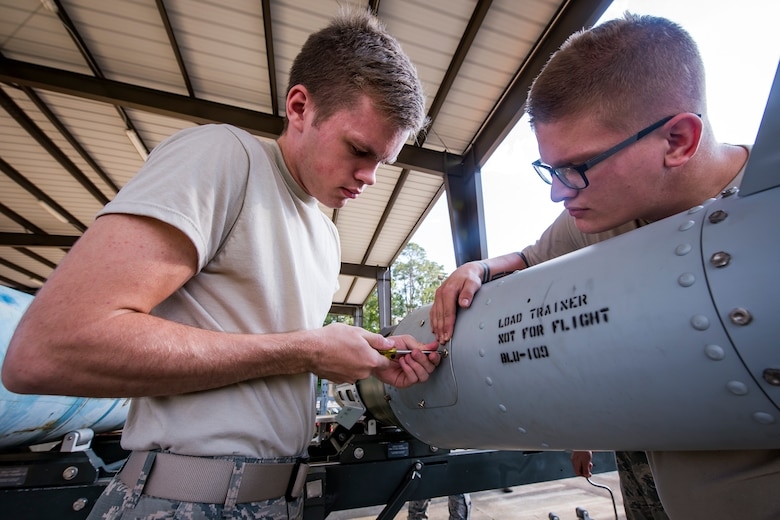 Airman 1st Class Hunter Westerlund, 23d Maintenance Squadron munitions specialist, screws a panel to a Joint-Direct Attack Munition (JDAM) during a bomb building course, May 10, 2018, at Moody Air Force Base, Ga.  To ensure readiness to complete their mission efficiently, Airmen practiced constructing a JDAM while wearing Mission Oriented Protective Posture gear to further simulate what their mission could entail. (U.S. Air Force photo by Airman 1st Class Eugene Oliver)