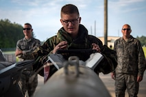 Senior Airman Joshua Hamilton, 23d Maintenance Squadron munitions crew chief, inspects the alignment of a Joint Direct Attack Munition (JDAM) during a bomb building course, May 10, 2018, at Moody Air Force Base, Ga. To ensure readiness to complete their mission efficiently, Airmen practiced constructing a JDAM while wearing Mission Oriented Protective Posture gear to further simulate what their mission could entail. (U.S. Air Force photo by Airman 1st Class Eugene Oliver)