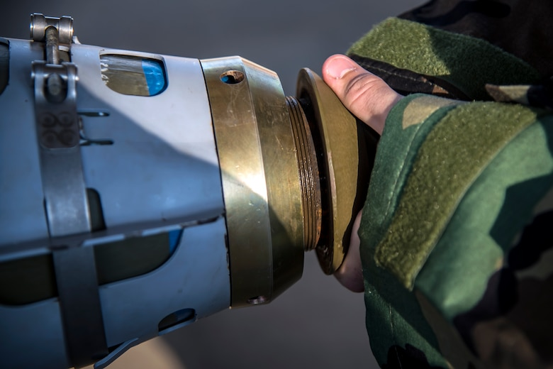 An Airman from the 23d Maintenance Squadron attaches a nose cone to a Joint Direct Attack Munition (JDAM) during a bomb building course, May 10, 2018, at Moody Air Force Base, Ga. To ensure readiness to complete their mission efficiently, Airmen practiced constructing a JDAM while wearing Mission Oriented Protective Posture gear to further simulate what their mission could entail. (U.S. Air Force photo by Airman 1st Class Eugene Oliver)
