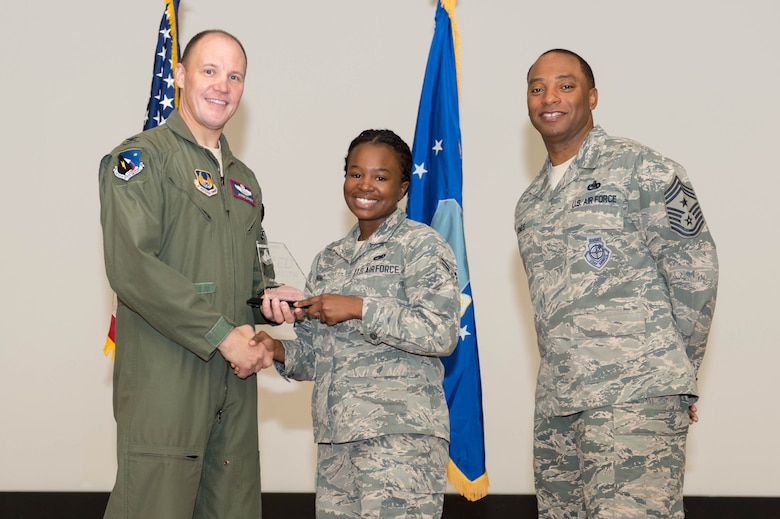 From left: Col. Jason Schott, 412th Test Wing vice commander, presents Airman 1st Class Tumarow Morning, 412th Maintenance Group, with the 412th TW Airman of the Quarter award, along with Chief Master Sgt. Roosevelt Jones, 412th TW command chief. The wing held its first quarter awards ceremony at the base theater May 3. (U.S. Air Force photo by Kyle Larson)