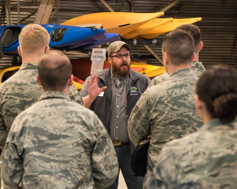 Tyler Glen, Outdoor Recreation director, speaks to speaks to Airman Leadership School graduates at Joint Base Elmendorf-Richardson, Alaska, May 10, 2018. The graduates took part in a new Pacific Air Forces-wide initiative for all ALS graduates to reinforce information obtained in Initial Supervisor Resiliency Training. At the forefront of this initiative is a bus tour the day after graduation, which offers an opportunity to see and interact with the programs and resources discussed during the course.