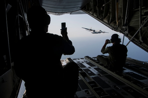 Two Hellenic air force loadmasters take photos of a U.S. Air Force C-130J Super Hercules, while riding on a Hellenic air force C-130H Hercules during an exercise Stolen Cerberus V interfly mission near Elefsis Air Base, Greece, May 10, 2018. The two aircraft flew in formation through different drop zones. (U.S. Air Force photo by Senior Airman Devin M. Rumbaugh)