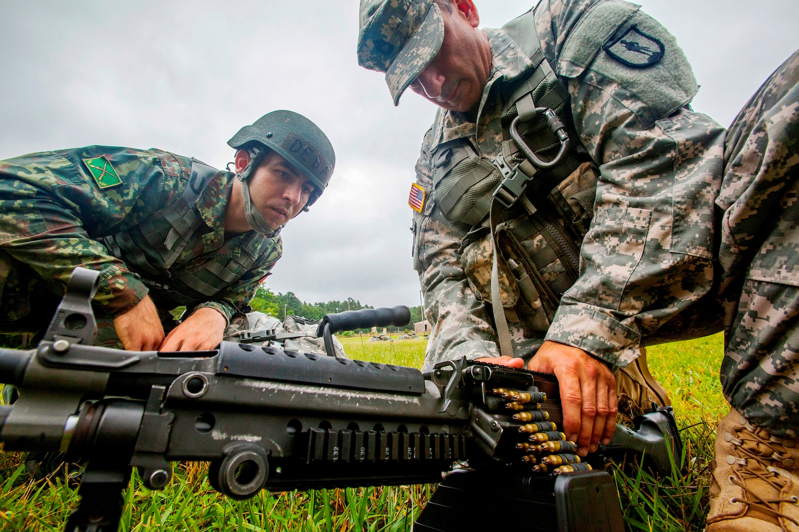 Sgt. 1st Class Harry R. Martinez, right, with the New Jersey Army National Guard, demonstrates how to load an ammunition drum on a M249 squad automatic weapon to Albanian Officer Candidate Endri Deda while training at Joint Base McGuire-Dix-Lakehurst, N.J. The New Jersey National Guard and Albania are paired together as part of the National Guard Bureau's State Partnership Program, which links National Guard elements with partner nations worldwide. The SPP began with three partnerships in 1993 and now, 25 years later, includes 74 partnerships spanning the globe.