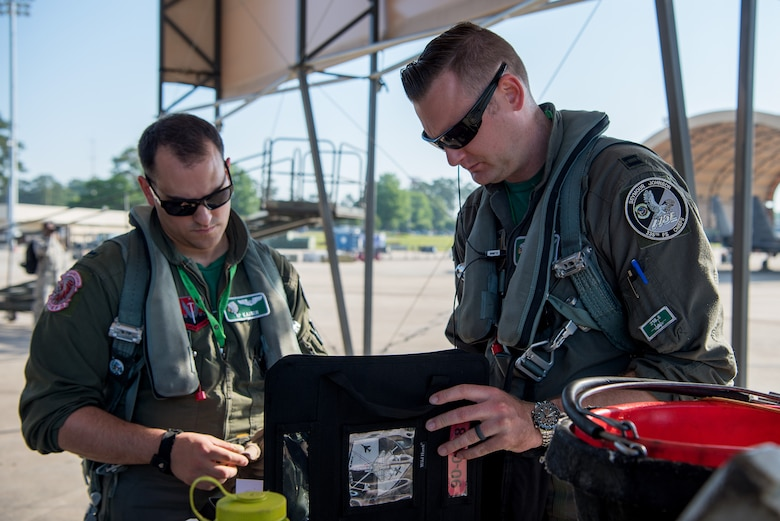 Capt. Bowman (right), 335th Fighter Squadron pilot, and 1st Lt. Kaiser, 335th FS weapon systems officer, check over the maintenance log of an F-15E Strike Eagle during exercise Razor Talon, May 11, 2018, at Seymour Johnson Air Force Base, North Carolina.