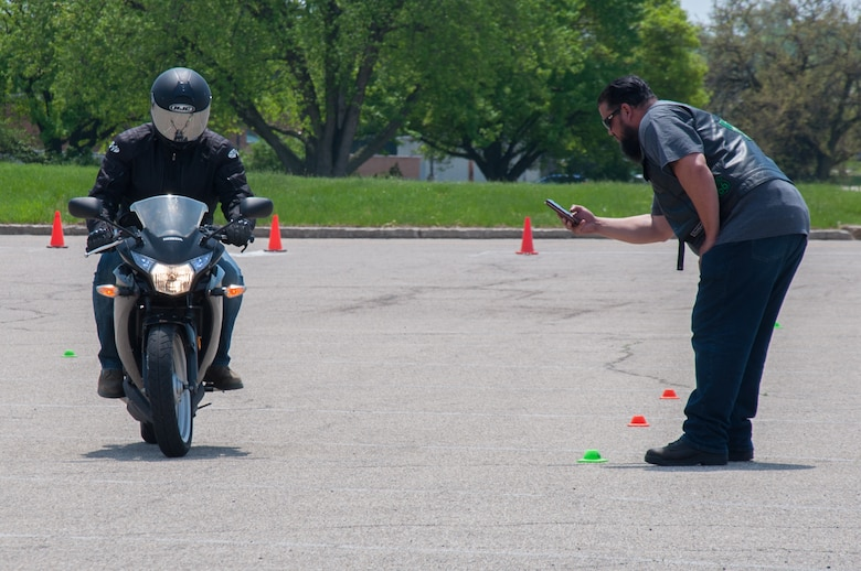 """Retired master sergeant and Green Knights member Joseph """"Smokey"""" Rivera times Staff Sgt. Ethan Cornell, a financial operations supervisor with the 88th Comptroller Squadron, during a slow ride contest as part of Wright-Patterson Air Force Base's Motorcycle Safety Day May 11, 2018."""