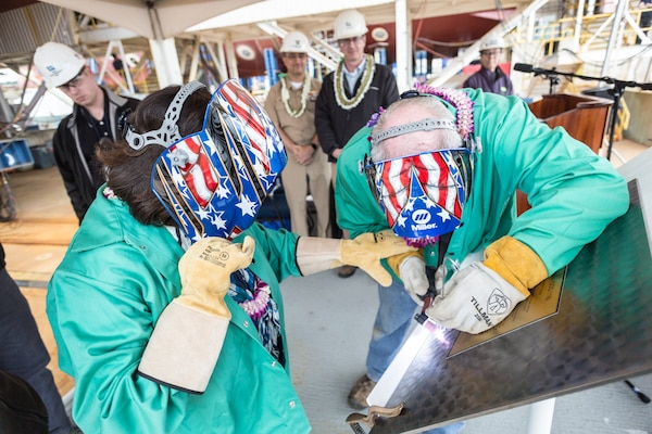 Irene Hirano Inouye (left), future USS Daniel Inouye (DDG 118) sponsor and wife of the late Sen. Daniel Inouye, and a Bath Iron Works employee etch Inouye's initials on to the keel plate during the ship's keel authentication ceremony in Bath, Maine, May 14.