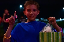 Child holds up index finger and prize bag as he smiles at the camera.