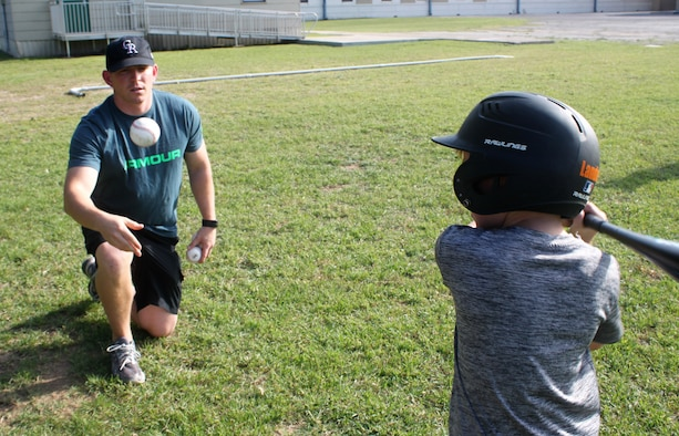 Master Sgt. Randy Alvis works with his son Landon on batting skills during youth baseball practice. Volunteers are the heart of youth sports, Alvis believes. (U.S. Air Force photo by Debbie Gildea)