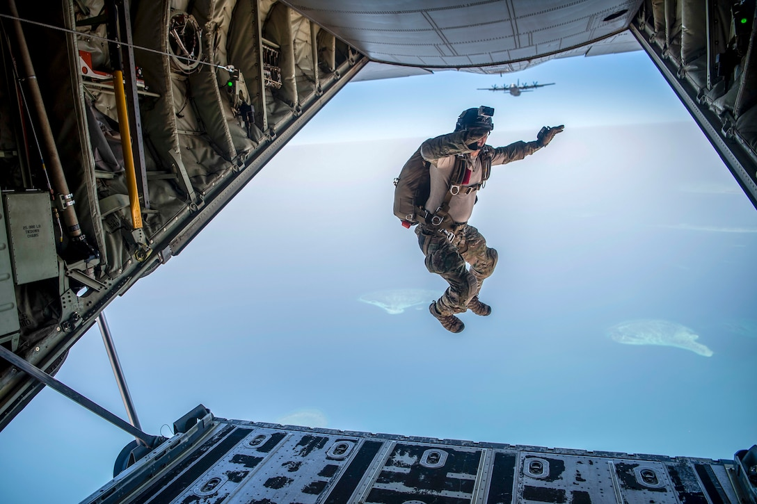 An airman jumps out of the back of the aircraft.