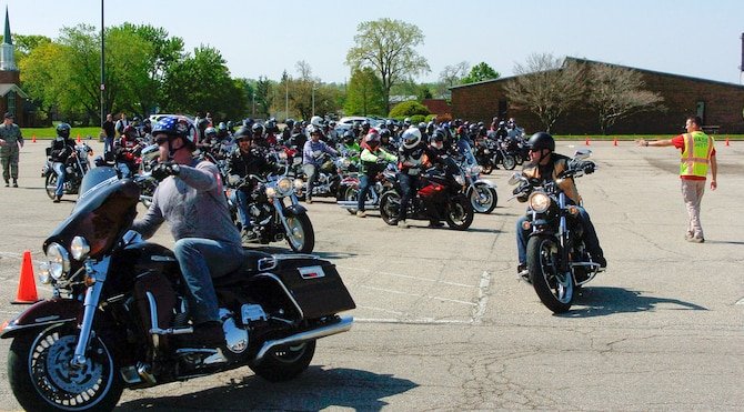 Staff Sgt. Zach Herick, Wright-Patterson Air Force Base Motorcycle Safety Day 2018 lead (right), directs more than 120 motorcycle riders as they depart on an optional 38-mile group ride as part of the event May 11.