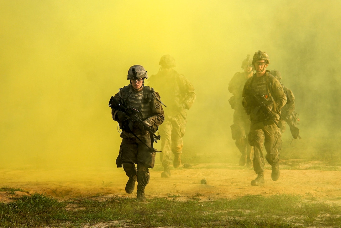 Soldiers move quickly through yellow smoke.
