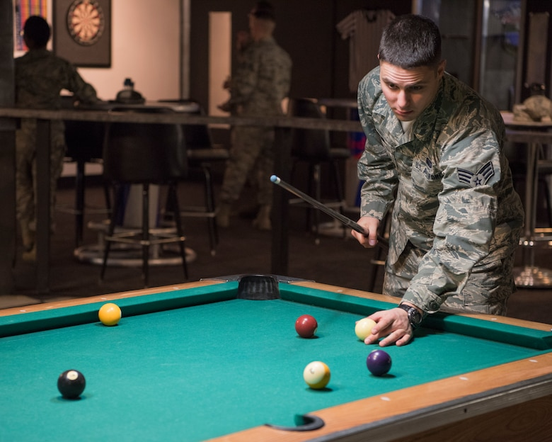 Senior Airman Michael Sadler, 673d Communication vulnerability hunt technician, plays pool at the Warrior Zone as part of an Initial Supervisor Resiliency Training bus tour at Joint Base Elmendorf-Richardson, Alaska, May 10, 2018. The tour is a new Pacific Air Forces-wide initiative for all ALS graduates, which offers an opportunity to see and interact with the programs and resources discussed during the course.